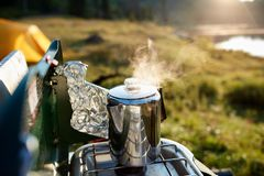 Steaming pot of coffee boiling on a gas burner. Outdoors on a camping trip in a close up view on a lake shore in morning light stock photography