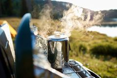 Steaming pot of coffee over a gas burner. At sunrise overlooking a tranquil lake on a camping trip royalty free stock photos