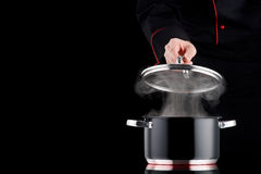 Steaming pot on induction cooker, modern chef in professio. Steaming black pot on induction cooker, modern chef in professional uniform in background stock photography