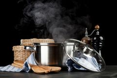 Steaming pot on black background. Steaming pot isolated on black background royalty free stock images