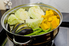 Steaming pot. Pumpkin, cabbage, beans, eggplant in steaming pot stock photos