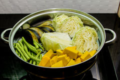 Steaming pot. Pumpkin, cabbage, beans, eggplant in steaming pot stock photography