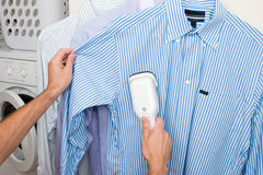 Steaming a shirt. By hand using a personal steamer Royalty Free Stock Image