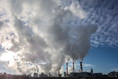 Steaming smoke stack and cooling tower with pollution. In big town stock photography