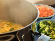 Steaming soup pot with broccoli and carrots. Steaming steel pot of meat soup with broccoli and carrots stock photos