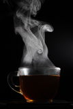 Steaming tea. A steaming cup of tea isolated on black background Stock Photos