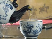 Steaming tea. Hot ready to drink prepared tea pouring steaming steam tea from flowered antique oriental teapot streaming a stream into and filling a white china Royalty Free Stock Photo