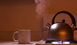 Steaming tea kettle. On stove with coffee cup Royalty Free Stock Image