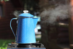 Steaming Vintage Coffee Pot. Steaming, vintage blue enamel coffee pot percolating on outdoor camping trip stock image