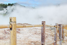 Steaming volcanic krator enclosed by a wooden fence Royalty Free Stock Photography