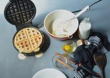 Steaming waffle iron making waffle, bowl of batter Royalty Free Stock Photo