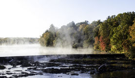 Steaming water on a cold Autumn morning. A cold morning overlooking a waterfall and Autumn color in Wallkill NY Stock Photos