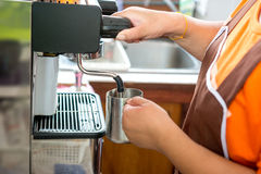Steaming water for hot cappuccino coffee with coffee machine Royalty Free Stock Photo