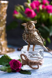 Steampunk bronze bird on glass cup on blue wooden tray. Stock Photography