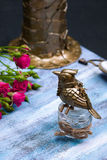 Steampunk bronze bird on glass cup on blue wooden tray. Stock Images