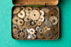 Steampunk gears collection in opened vintage box. closeup, green paper background. Shallow depth of field, soft focus Stock Photos