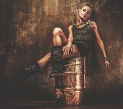 Steampunk girl on a barrel. Attractive steampunk girl sitting on barrel Royalty Free Stock Photo
