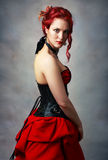 Steampunk girl. Beautiful steampunk girl with bodypainting on her shoulder posing at studio in black corsette and red skirt stock image