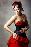 Steampunk girl. Beautiful steampunk girl with bodypainting on her shoulder posing at studio in black corsette and red skirt stock images