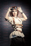 Steampunk girl with goggles. Beautiful redhair girl with steampunk Goggles standing on a brick wall background Royalty Free Stock Photos