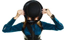 Steampunk girl with hat. Young steampunk islolated girl on white holding fancy hat. Fantasy old fashion covering face with topper and goggle royalty free stock photography