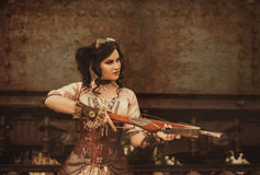Steampunk girl. A steampunk girl hunts with a crossbow. Old train background. Creative colors stock photography