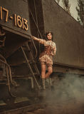 Steampunk girl. A steampunk girl is riding a train. Old retro train background. Creative colors royalty free stock photos