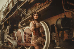 Steampunk girl. A girl in steampunk style posing with a wrench. Old retro train background. Creative colors stock images