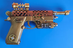 Steampunk Hand Cannon. Steampunk style future pistol. On a dark blue background royalty free stock image