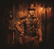 Steampunk mężczyzna z pistoletem na rocznika steampunk tle Zdjęcia Stock