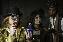 Steampunk with Magnifying Glass. Steam Punks in Underground Lair with Potion and Magnifying Glass Stock Image