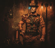 Steampunk man with gun on vintage steampunk background.  Stock Photo