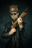 Steampunk man in a hat with gun. Steam punk culture. Toned Stock Images