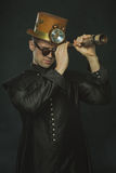 Steampunk man in a long coat looking through a telescope. Royalty Free Stock Photos