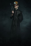 Steampunk man in a long coat smoking a pipe. Stock Photos