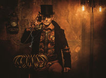 Steampunk man with Tesla coil on vintage steampunk background Stock Images