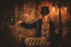 Steampunk man with Tesla coil on vintage steampunk background.  Stock Photography