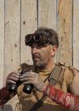 Steampunk man wearing glasses looks through a binoculars Stock Image