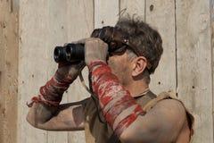 Steampunk man wearing glasses looks through a binoculars Stock Photography