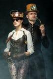 Steampunk par Man med ett rör och en flicka med exponeringsglas och H Royaltyfri Foto