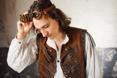 Steampunk pilot in a leather vest and flight glasses on his forehead. stock photos