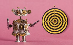 Steampunk robot handyman with screw drivers and dart board, vintage yellow black shooting target red center. Pink. Steampunk robot handyman with screw drivers Royalty Free Stock Photography