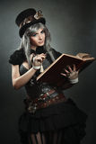 Steampunk scientist with book and lens Stock Photos
