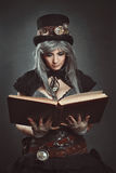 Steampunk scientist with book. Steampunk scientist with open book in hand royalty free stock images