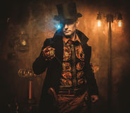 Steampunk style man with various mechanical devices on vintage steampunk background royalty free stock image