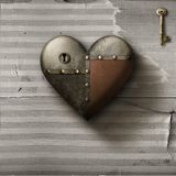 Metal patched heart with key on old paper background Stock Images