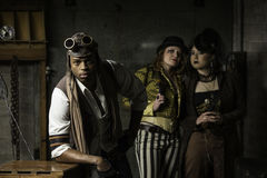 Steampunk Trio. Young Steam Punks PosIng in Underground Lair Stock Photo