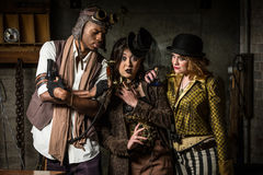 Steampunk Trio with Phone. Three Steampunks with Underground Lair with Retro Phone Stock Image