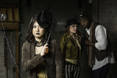 Steampunk Trio. Young Steam Punks PosIng in Underground Lair Stock Image