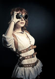 Steampunk woman looking over her goggles. Beautiful redhair steampunk woman looking over her goggles aside on the black backgroud Royalty Free Stock Photo